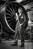 Environmental black and white portrait of young aviation apprentice in front of a jet engine at BAE systems.