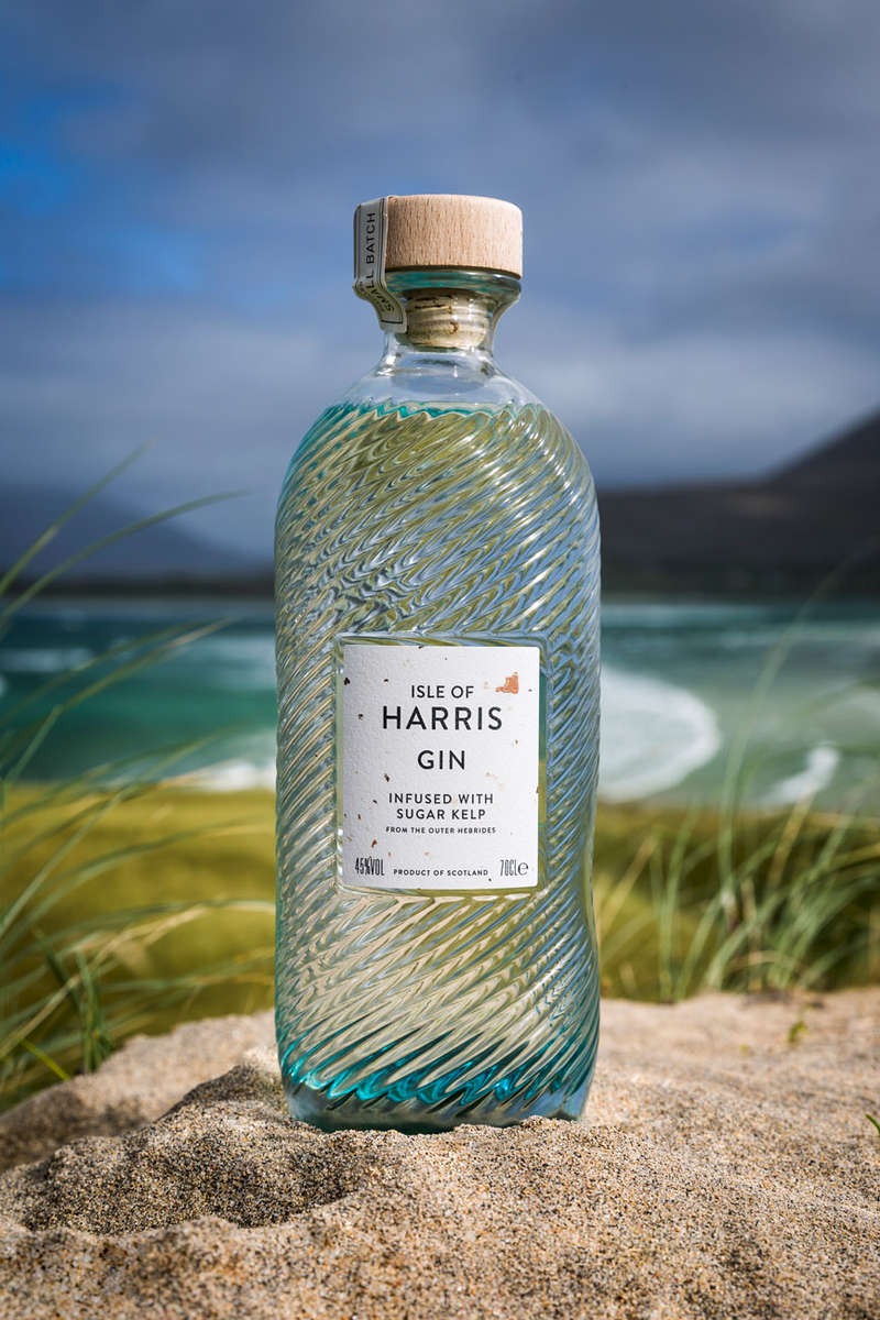 bottle of harris gin sitting on the sand on the beach on a sunny day