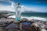 a bottle of Harris gin sitting on the rocks by the sea on isle of harris