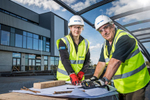 Environmental portrait of young apprentice with mentor at work with building plans