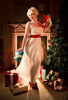 1950's style christmas burlesque photograph of a girl with a present in a sheer night dress