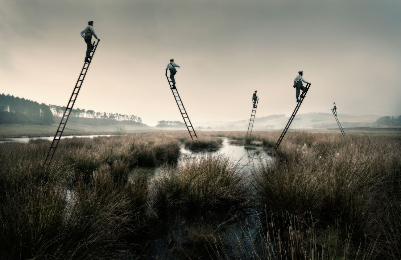 men on top of ladders hanging in the air unsupported