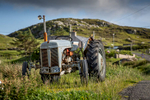 beautiful old tractor by the side of a road in evening light on the isle of harris.
