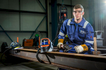 Environmental portrait of young apprentice at work in a factory