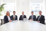 Corporate group portrait of people in an office sitting around a desk.