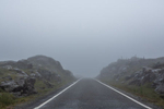 misty single track road with hills either side n isle of harris. road dissapearing into the fog