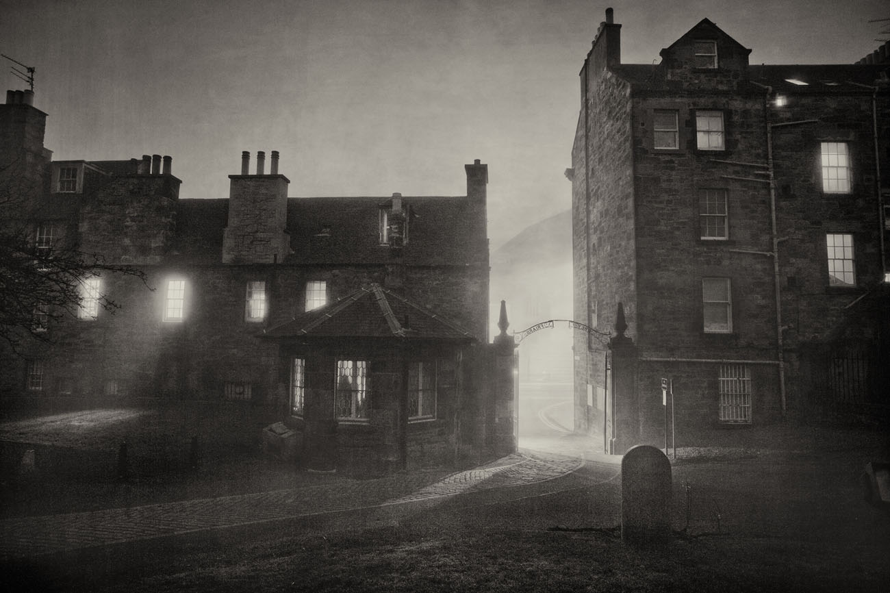graveyard view with backs of houses in Greyfriars kirk in Edinburgh. Black and white photo on a foggy night.