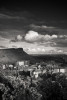 beautiful black and white view of Arthurs seat from Calton Hill, Edinburgh on a sunny day with a moody dark sky