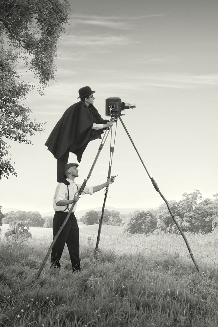 a man stands on the shoulders of another to film with a vintage film camera resting on a home made wooden tripod