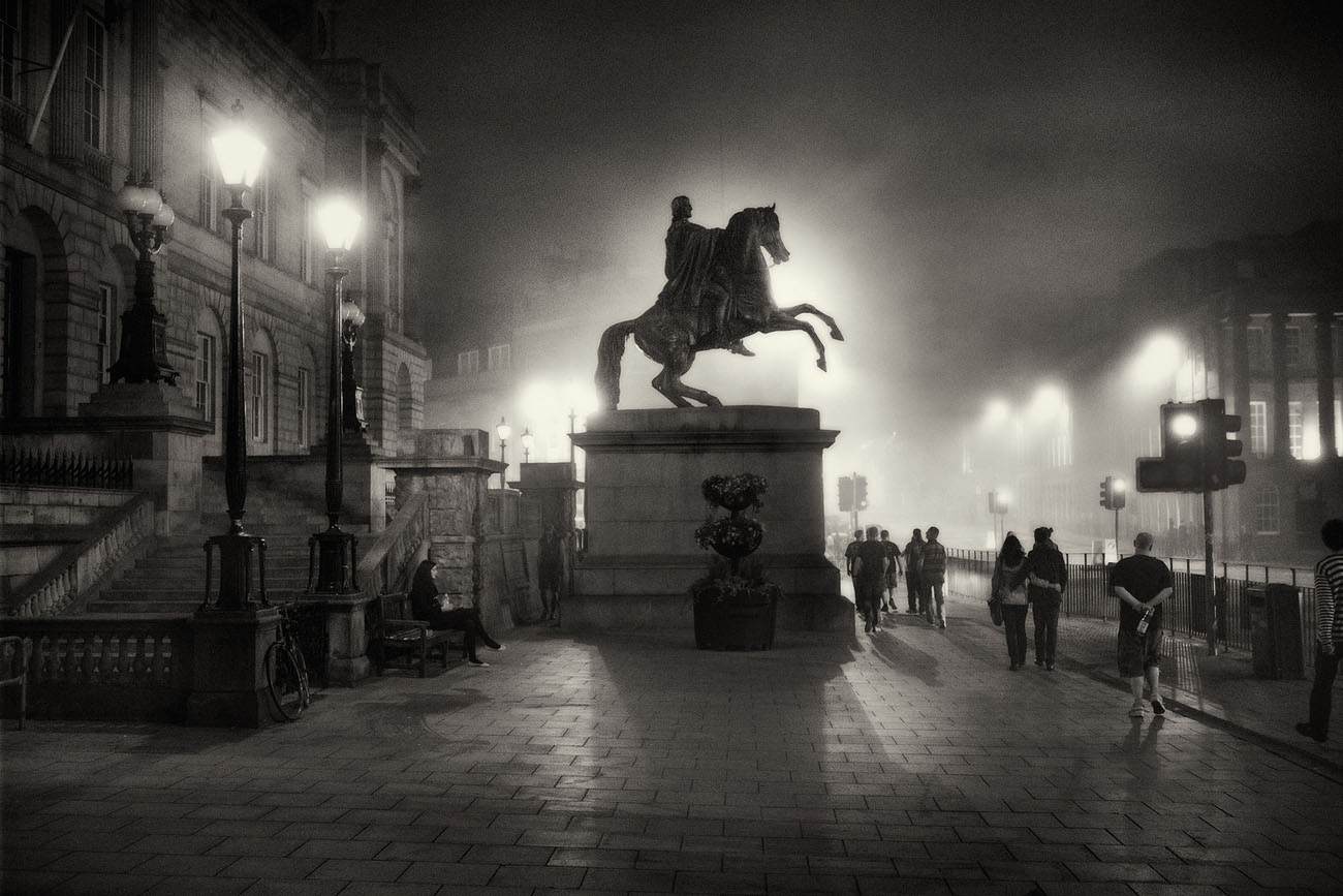 silhouette of a statue of a man on a horse. Edinburgh Princes Street on a foggy night