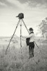 a man stands in a field holding a giant tripod with a film camera on it. Black and white