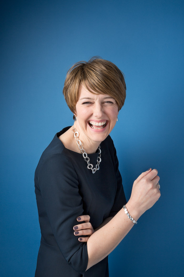 business woman laughing against blue background