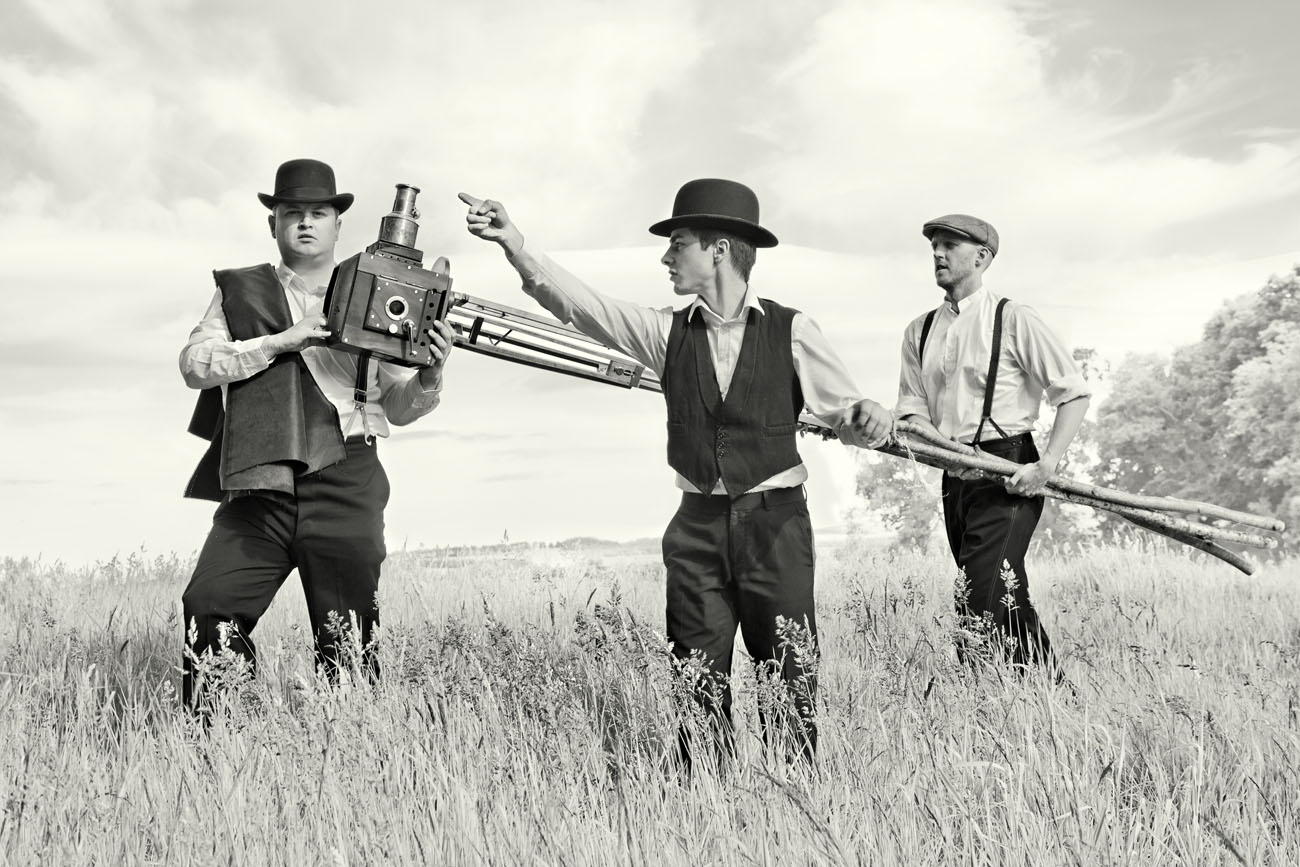 a man in vintage bowler hat directs two others with a film camera on a giant tripod. Black and white photograph