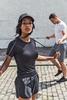 modellswearing Tombo sportswear on a cobbled street skipping