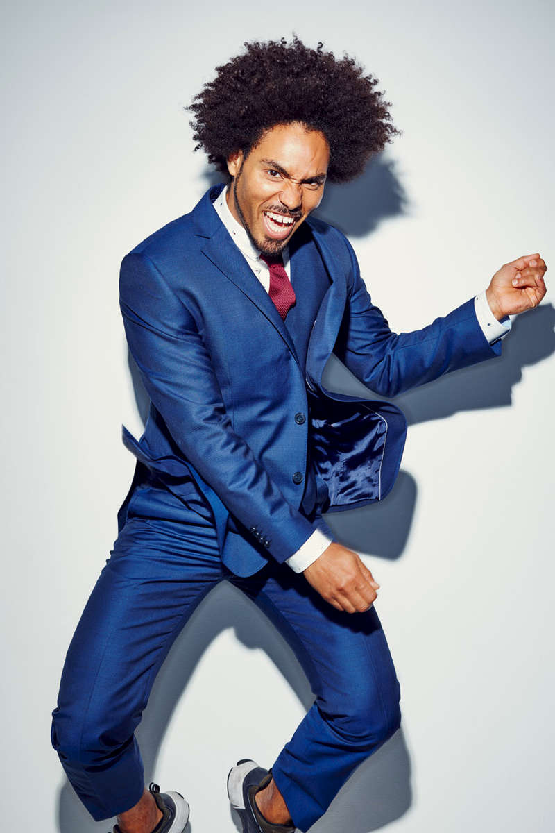 High energy studio fashion portrait of a black man in a blue suit leaping in the air