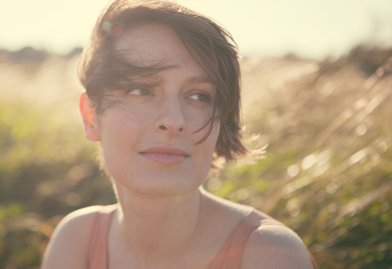 beauty photo of girl in summer field back lit