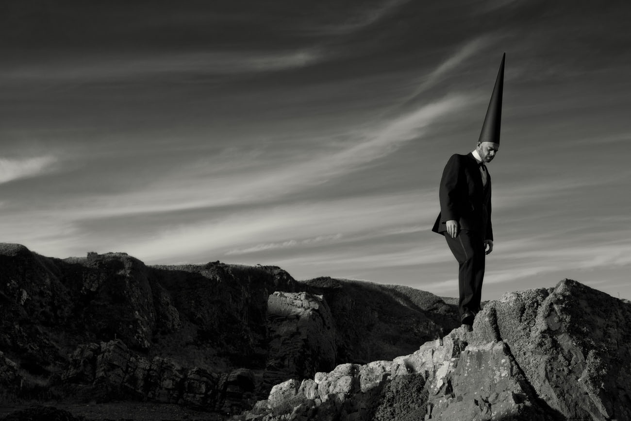 Coneman standing on cliffs by the sea. B+W