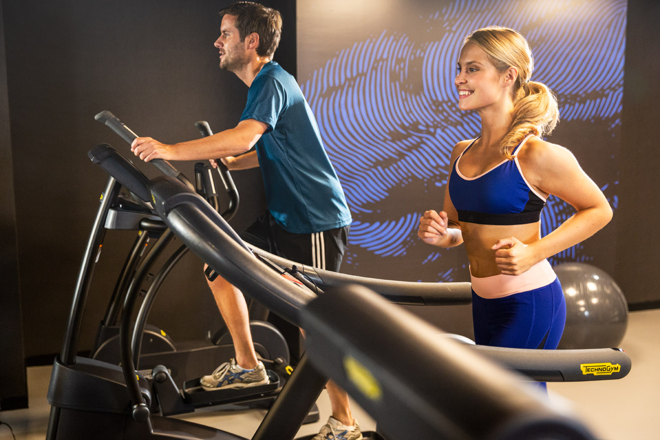 young couple using machines in a hotel gym