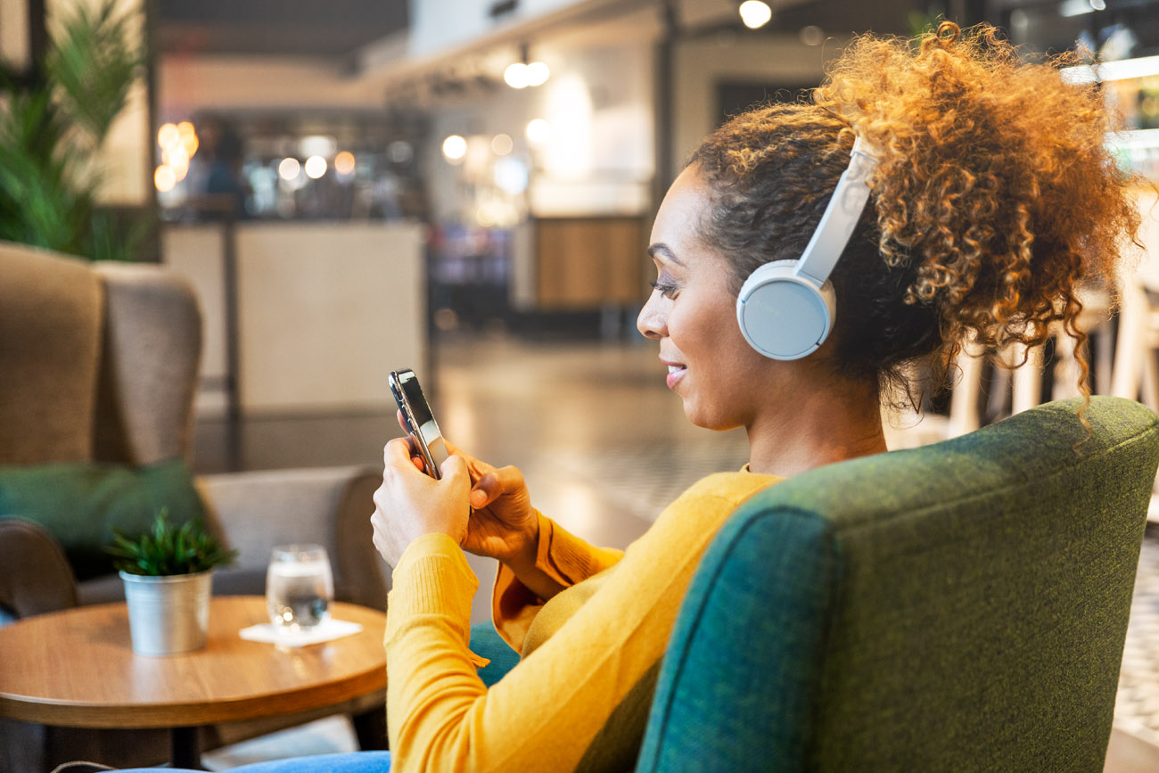 black woman listening to music on headphones in a luxury hotel