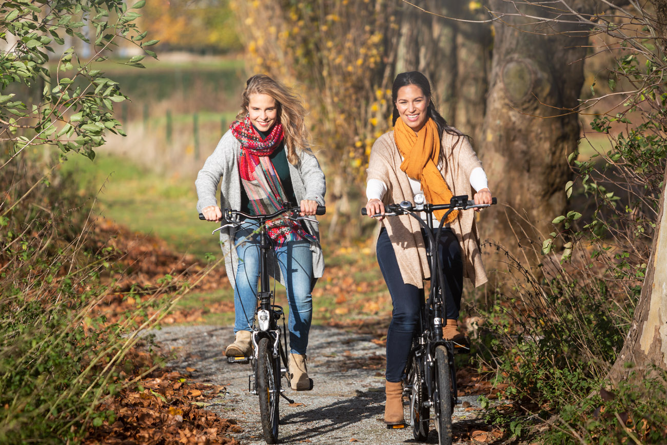 two women cycling through a beautiful forest in autumn
