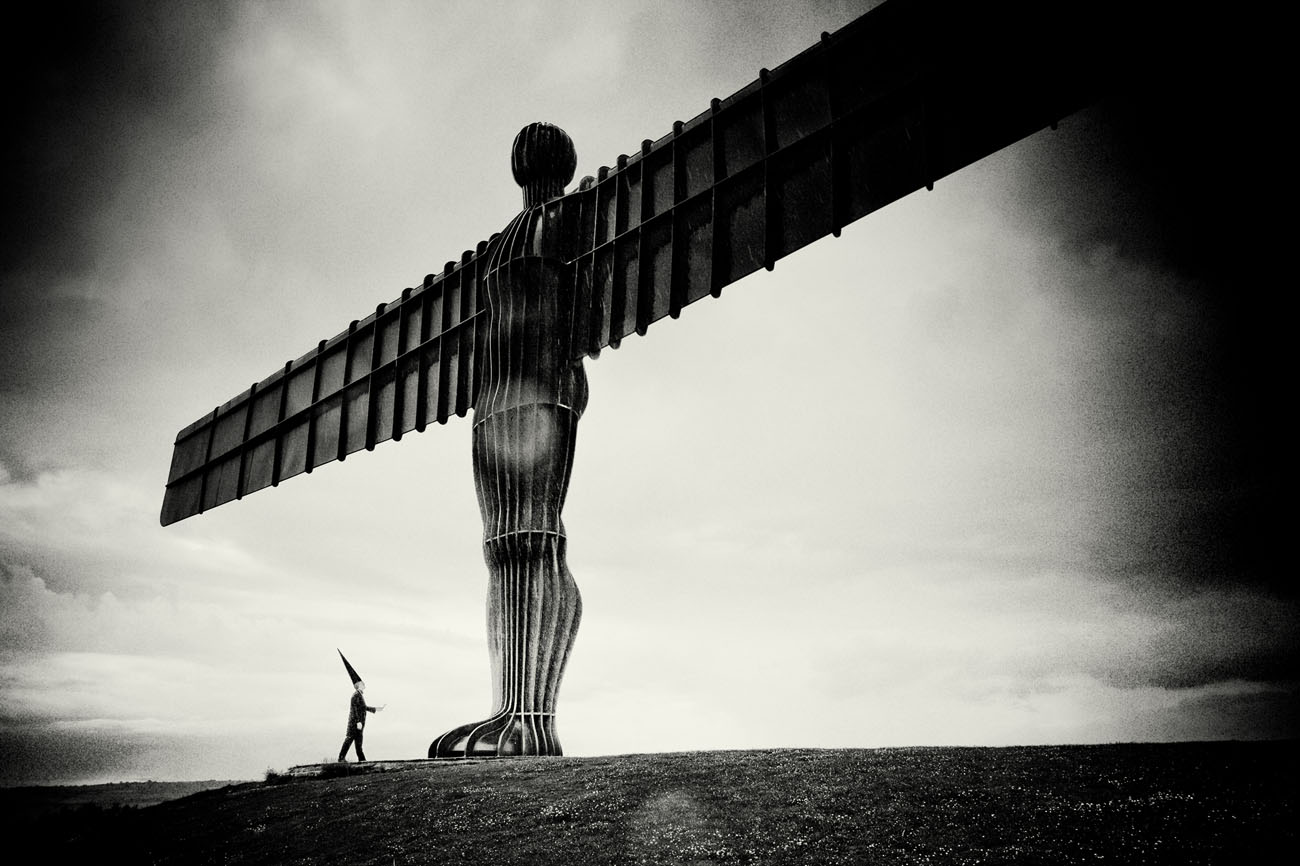 Coneman holds a feather up, standing at the foot of the Angel of the North