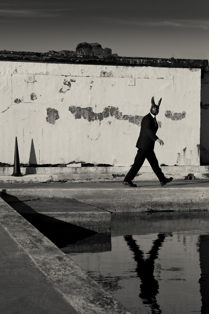 a man in a black suit and dark hare's mask walks in front of an outdoor pool in a black and white photograph.
