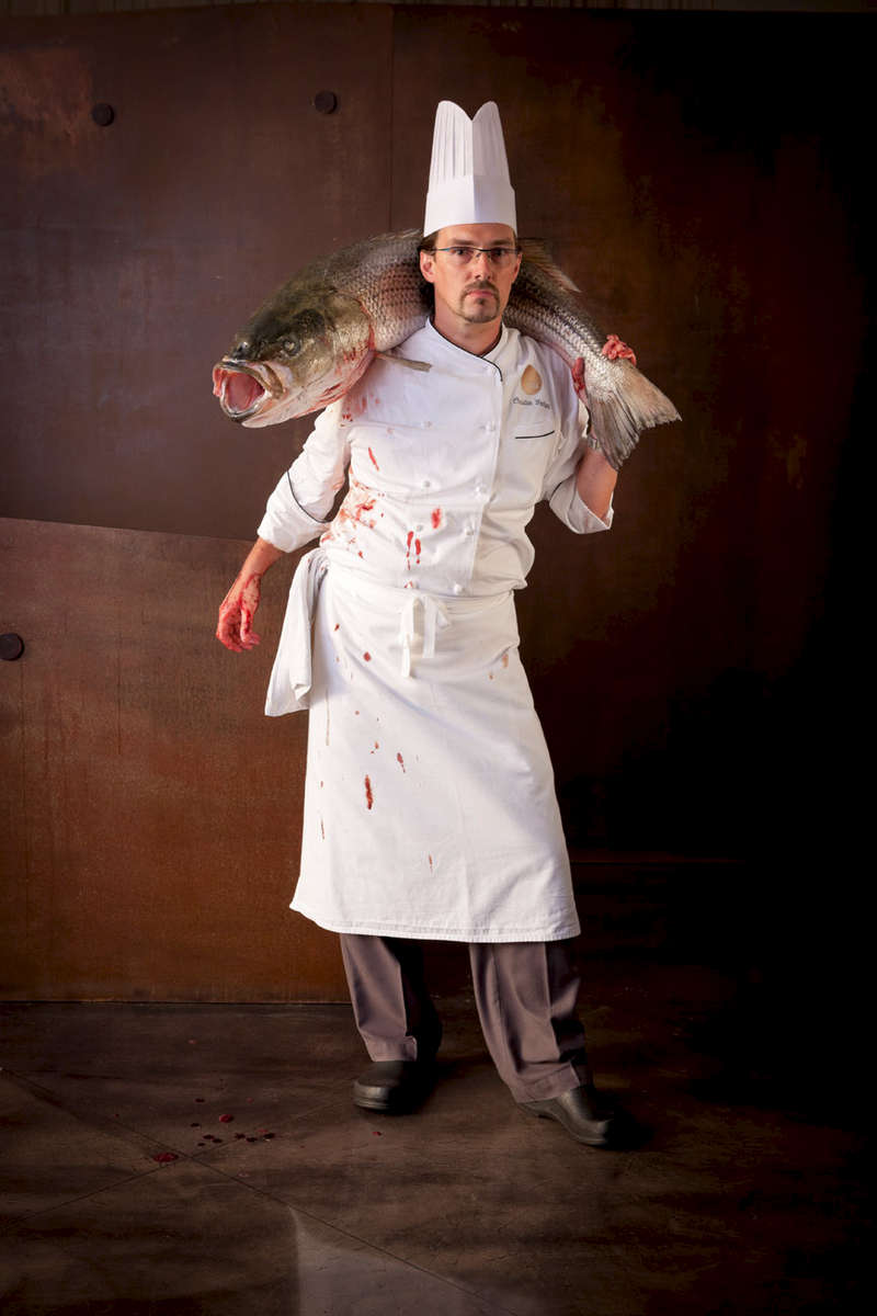 chef in whites holding a huge salmon round his neck