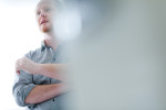 portrait of a man behind a blurred laptop. Corporate portraiture in high key