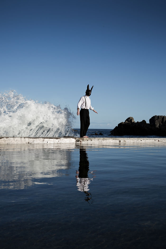 a man in a hare mask about to be swamped by a wave