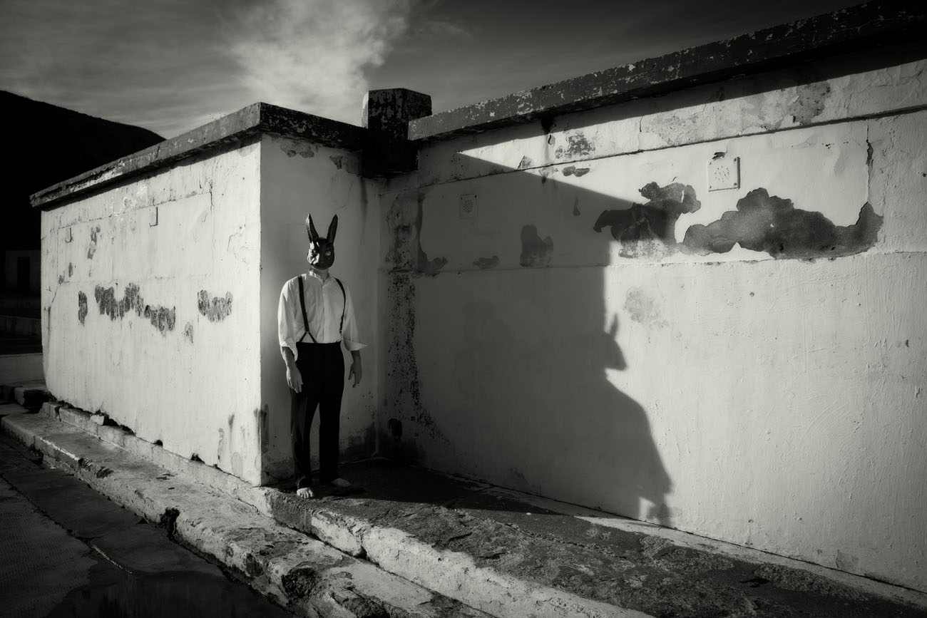 a man in a black suit and dark hare's mask stands in the shadows of a ruined building in a black and white photograph.