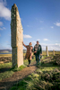 Historic Scotland  - ring of Brodgar on Orkney with a woman touching a standing stone