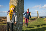 Historic Scotland  - child hiding behind a standing stone at the ring of Brodgar on Orkney