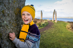 Historic Scotland  - smiling boy by a standing stone at ring of Brodgar on Orkney