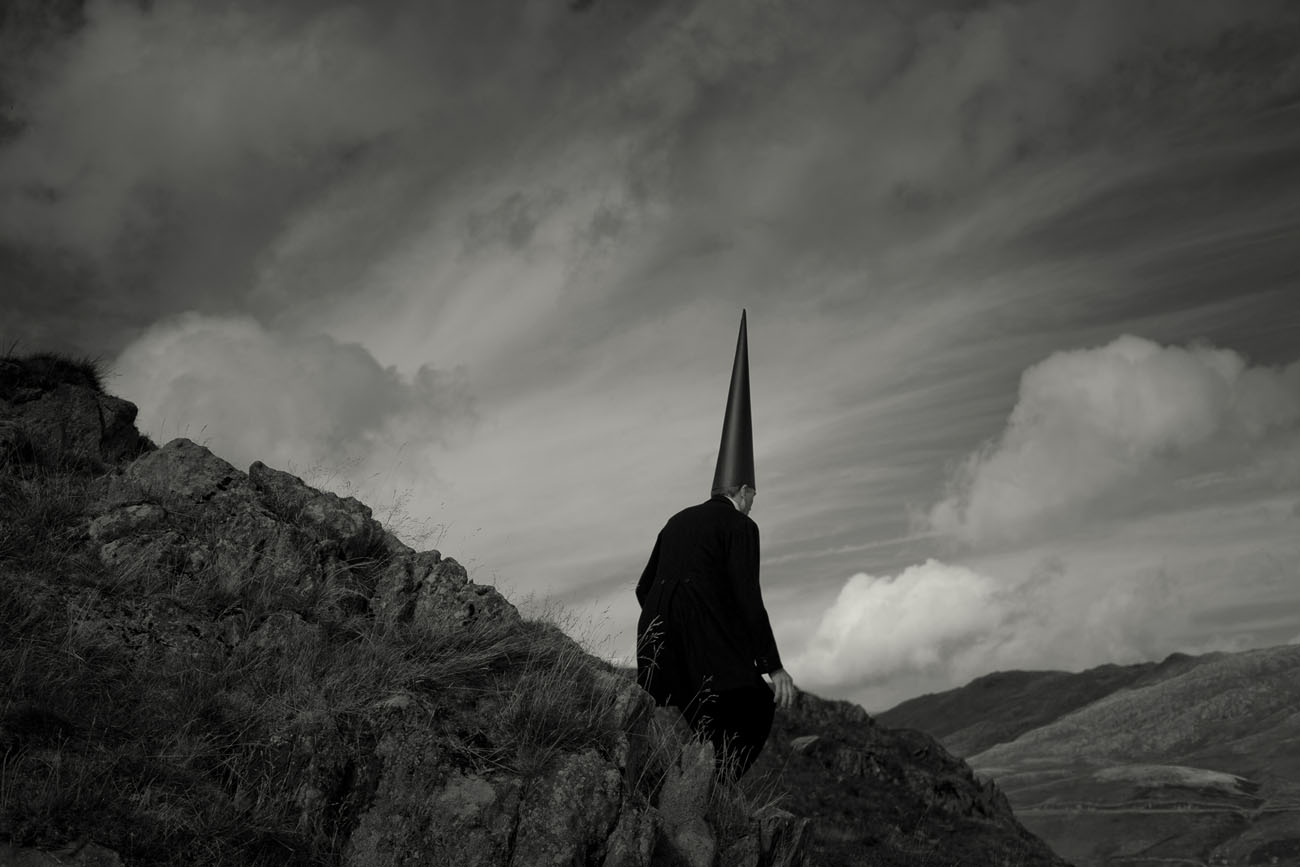 Coneman resting on a rock in the mountains. Black and white photograph