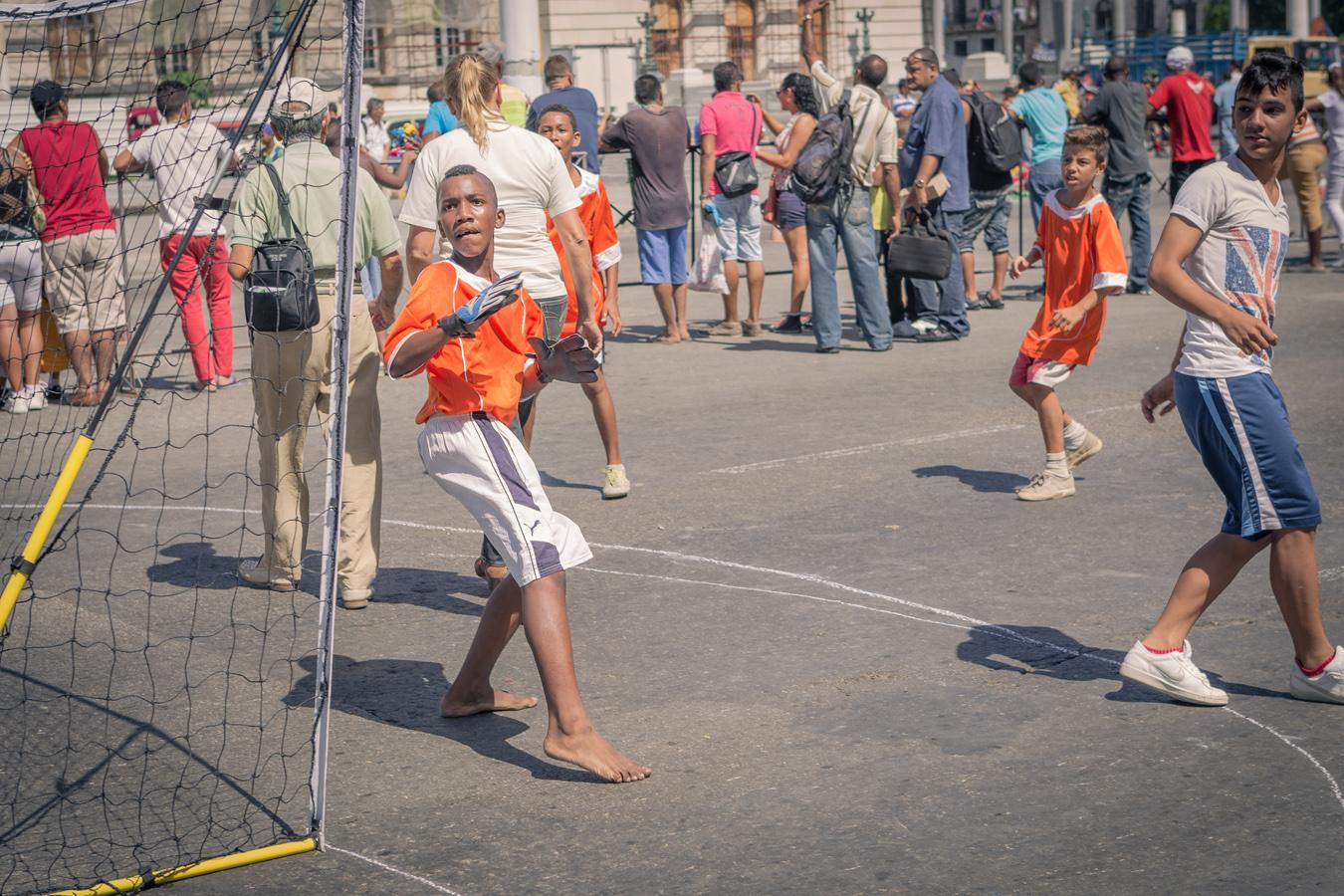 barefoot kid paying football in Havana