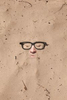 a mans face appearing in the sand