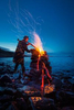 a man performas a ritual at a burning fire cairn on the edge of the sea.
