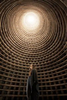 a girl stands inside a surreal round building with a bright light above. girl inside a dovecot