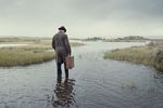 a man with a hat and suitcase stands in a loch on Rannoch,