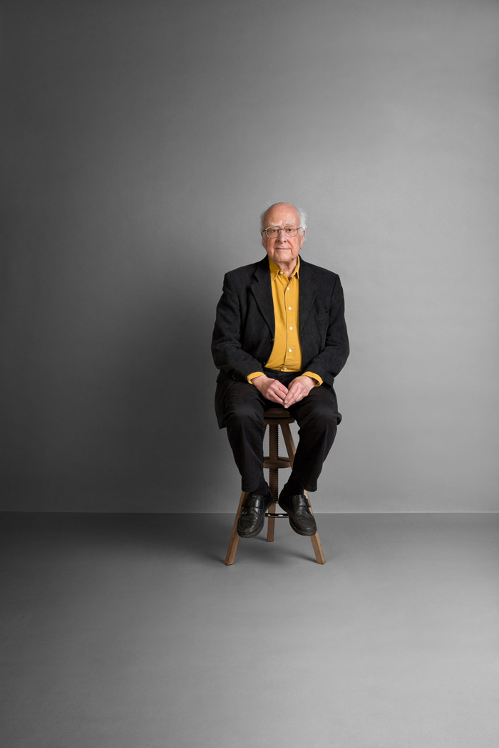 portrait of professor Peter Higgs the discoverer of the Higgs Bosun. Sitting on a stool in an empty room