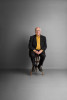 portrait of professor Peter Higgs the discoverer of the Higgs Boson. Sitting on a stool in an empty room