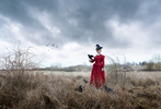 Anne Marie Duff. Woman in 17th century red dress standing in a thorny field with a crow on her arm