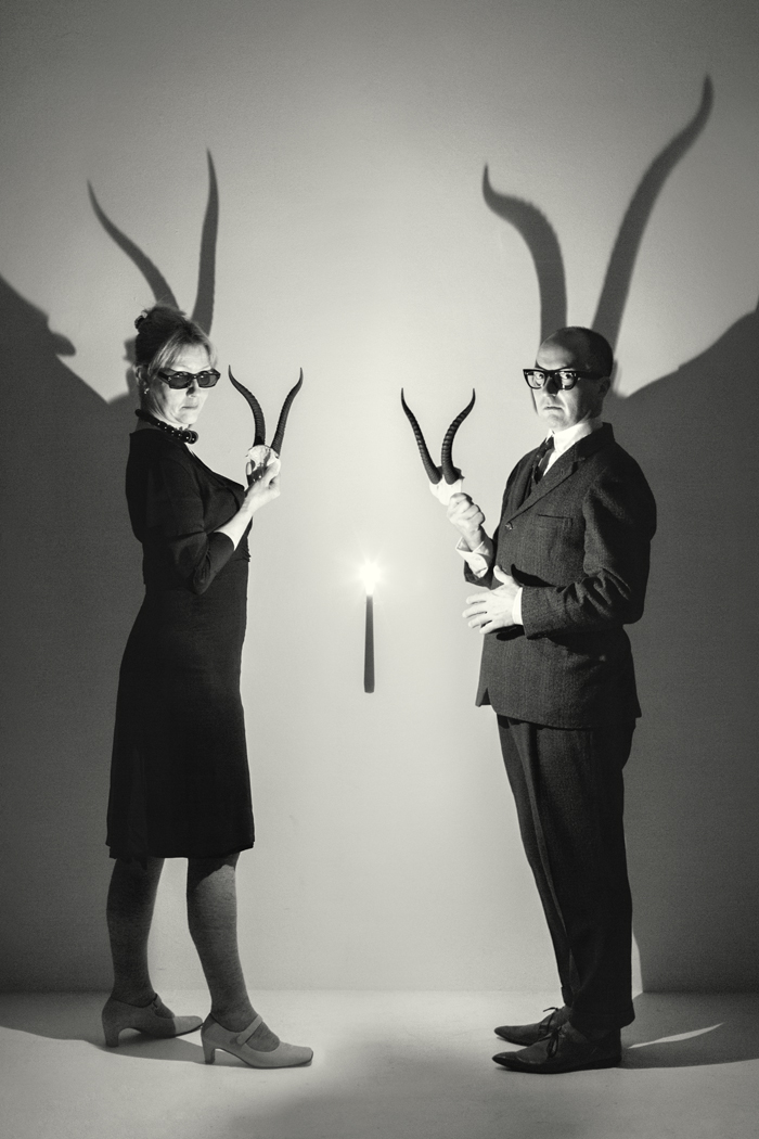 A couple standling in a studio holding Dorcus horns lit by a single  candle with horn shadows