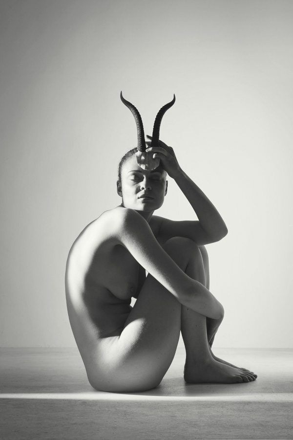 seated nude woman in a studio holding horns to her forehead