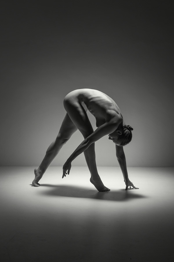 naked woman in a moody lit studio bending down making abstract shape. Fine art nude of a beautiful woman.