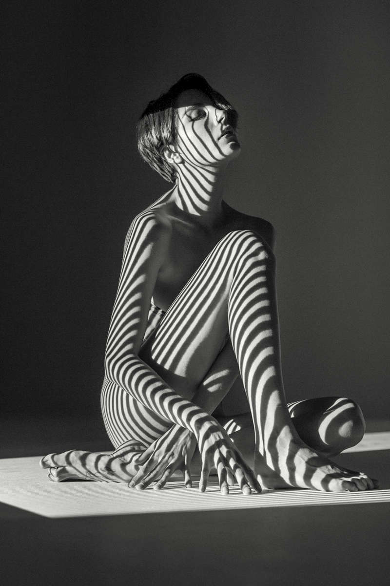 Roarie Yum seated nude with stripes projected on her naked body