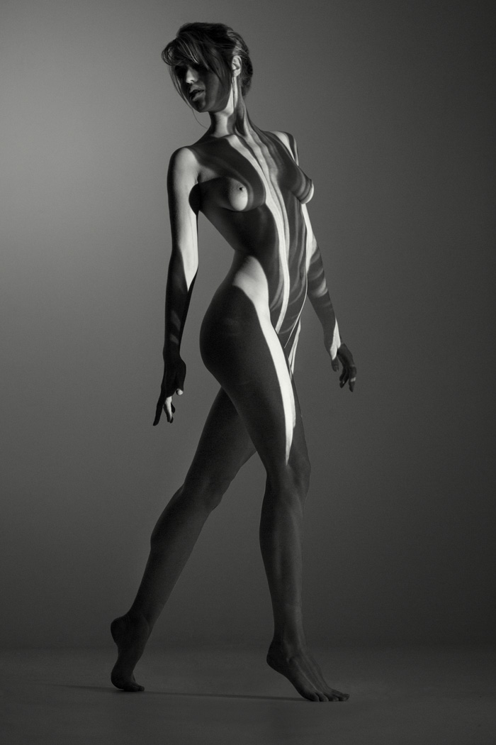 nude woman in studio with projector light