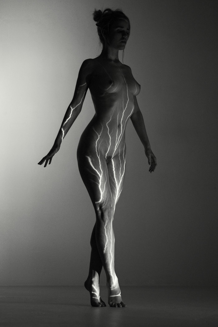 nude woman lit with a lightening stripe projector in a studio. Black and white art nude