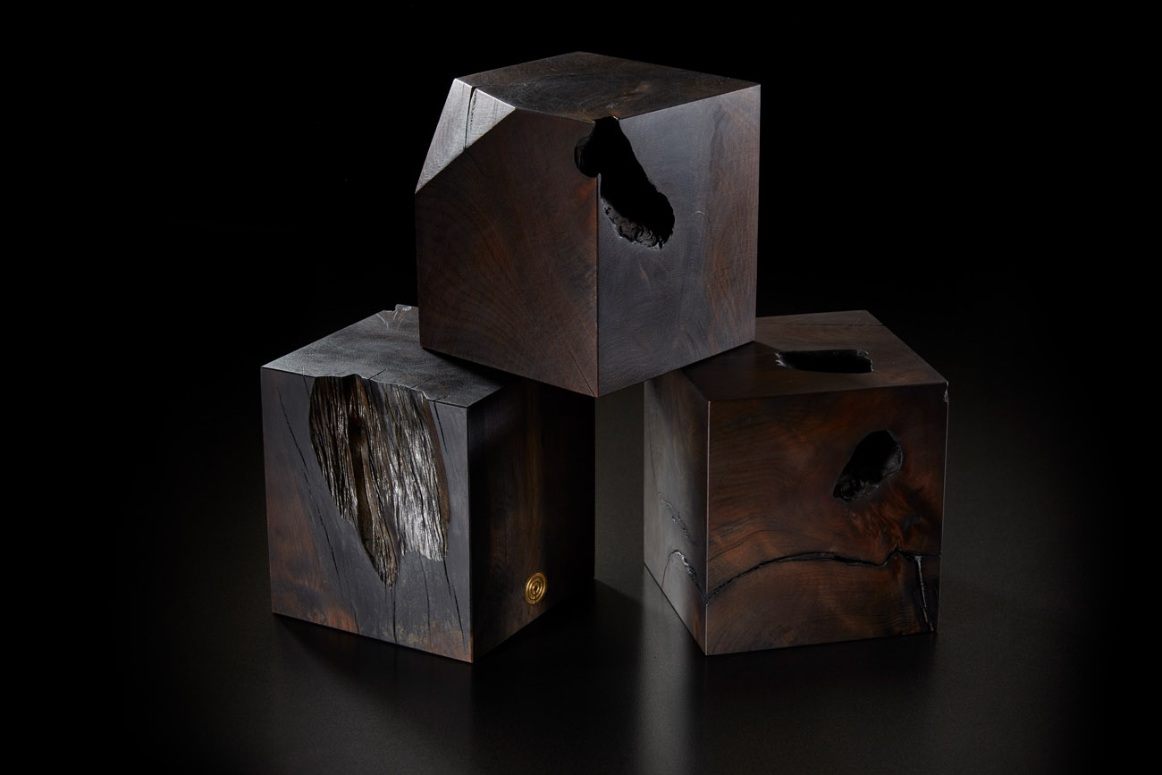 finely crafted bespoke black wooden cubes stacked in a studio on a black background