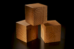 finely crafted bespoke  wooden cubes with celtic designs stacked in a studio on a black background